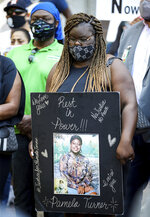 Chelsie Ruben holds a sign asking for justice for her mother Pamela Turner during a press conference in which attorney Benjamin Crump announced the filing of a federal lawsuit against Baytown Police officer Juan Delacruz in the death of Turner, outside the Harris County Civil Courthouse on Thursday, April 8, 2021, in Houston. Turner, who would have turned 46 years old today, was shot and killed on May 13, 2019. (Godofredo A. Vásquez/Houston Chronicle via AP)