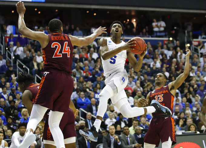 Duke forward RJ Barrett (5) drives to the basket past Virginia Tech forward Kerry Blackshear Jr. (24) and guard Ahmed Hill (13) during the second half of an NCAA men's East Regional semifinal college basketball game in Washington, Friday, March 29, 2019. (AP Photo/Alex Brandon)
