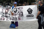 Anti-racism groups hold a banner with figures a