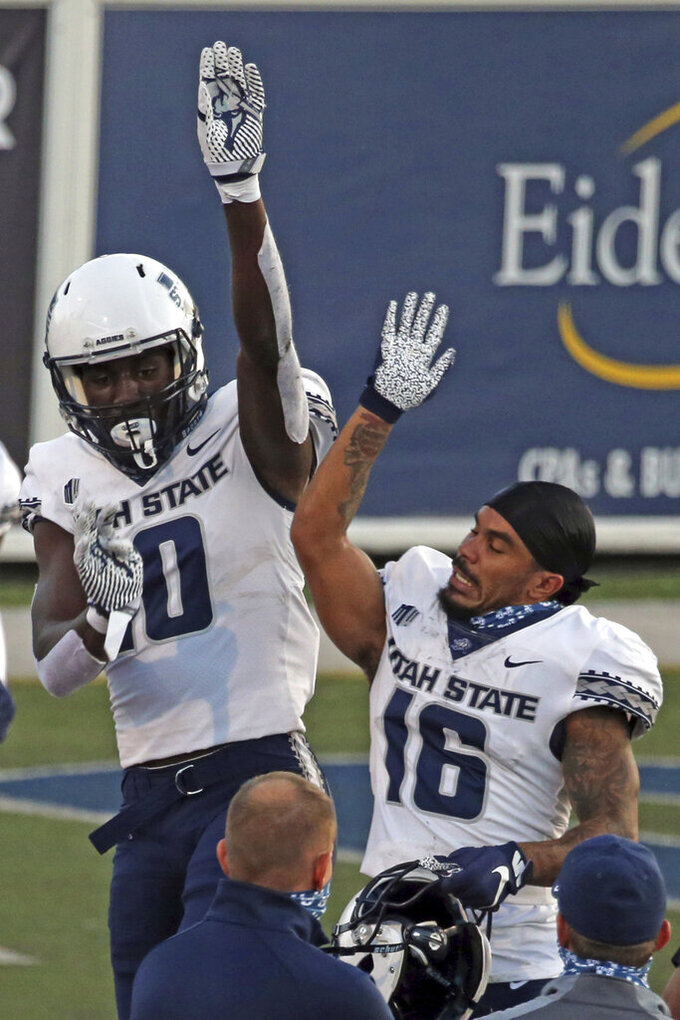 Utah State's Justin McGriff (10) celebrates his touchdown reception with Cam Lampkin (16) during the first half of an NCAA college football game against Nevada on Thursday, Nov. 5, 2020, in Reno, Nev. (AP Photo/Lance Iversen)