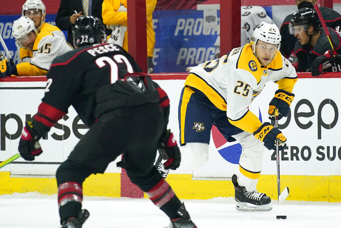 Nashville Predators right wing Mathieu Olivier (25) controls the puck while Carolina Hurricanes defenseman Brett Pesce (22) defends during the first period in Game 1 of an NHL hockey Stanley Cup first-round playoff series in Raleigh, N.C., Monday, May 17, 2021. (AP Photo/Gerry Broome)