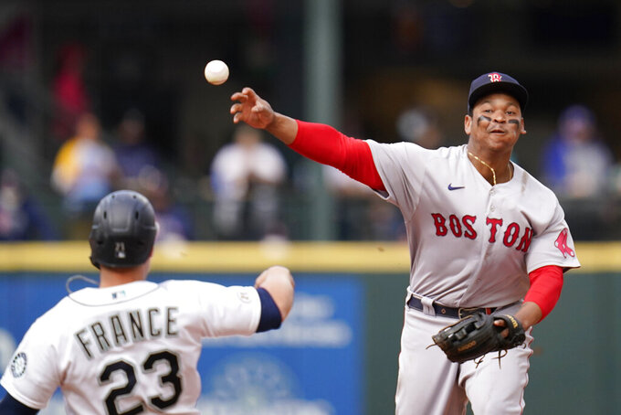 Boston Red Sox third baseman Rafael Devers throws to first base after forcing out Seattle Mariners' Ty France at second in the sixth inning of a baseball game Wednesday, Sept. 15, 2021, in Seattle. Mariners' Abraham Toro was out at first on the double play. (AP Photo/Elaine Thompson)
