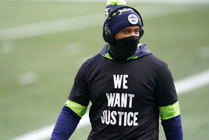 "Seattle Seahawks quarterback Russell Wilson wears a T-shirt that reads ""We Want Justice"" in support of Black Lives Matter as he warms up for an NFL football game against the New York Giants, Sunday, Dec. 6, 2020, in Seattle. (AP Photo/Elaine Thompson)"