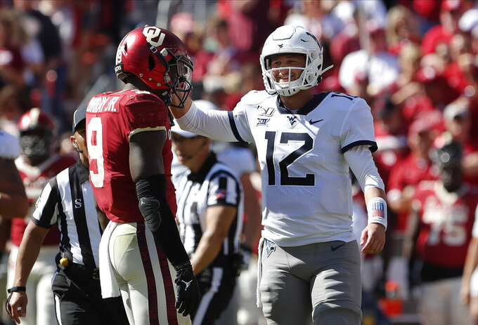 West Virginia quarterback Austin Kendall (12) jokes around with Oklahoma linebacker Kenneth Murray (9) between plays in the second half of an NCAA college football game in Norman, Okla., Saturday, Oct. 19, 2019. Oklahoma won 52-14. (AP Photo/Alonzo Adams)