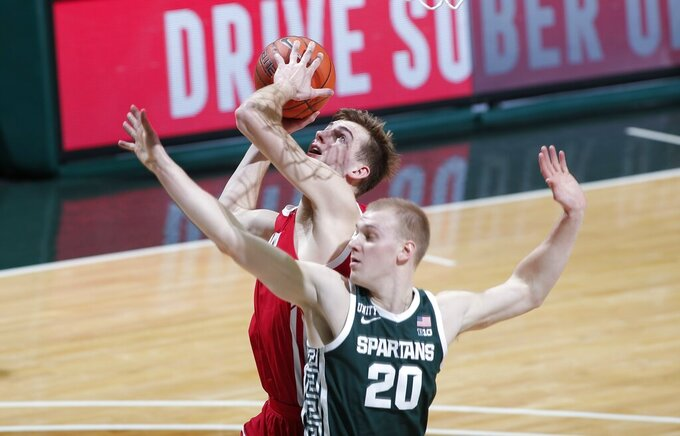 Wisconsin's Tyler Wahl, left, shoots against Michigan State's Joey Hauser (20) during the first half of an NCAA college basketball game, Friday, Dec. 25, 2020, in East Lansing, Mich. (AP Photo/Al Goldis)