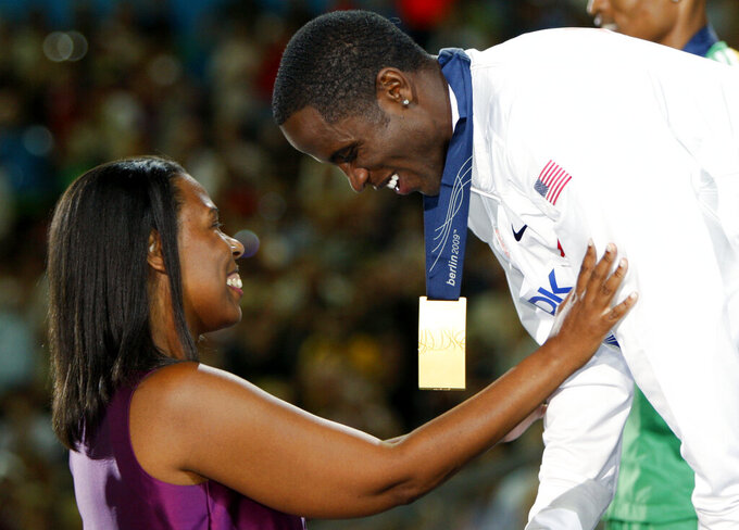 FILE - In this Aug. 22, 2009, file photo, United States' Dwight Phillips, right, receives his gold medal from Jesse Owens' granddaughter, Marlene Dortch, left, during the medal ceremony for the Men's Long Jump at the World Athletics Championships in Berlin,. (AP Photo/Markus Schreiber, File)