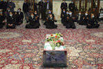 In this picture released by the Iranian Defense Ministry and taken on Saturday, Nov. 28, 2020, people pray over the flag draped coffin of Mohsen Fakhrizadeh, an Iranian scientist linked to the country's disbanded military nuclear program, who was killed on Friday, during a funeral ceremony at the Imam Reza holy shrine in the northeastern city of Mashhad, Iran. An opinion piece published by a hard-line Iranian newspaper has suggested that Iran must attack the Israeli port city of Haifa if Israel carried out the killing of a scientist. (Iranian Defense Ministry via AP)