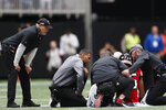 Atlanta Falcons head coach Dan Quinn watches medical teams attend to Atlanta Falcons running back Ito Smith (25) during the first half of an NFL football game against the Los Angeles Rams, Sunday, Oct. 20, 2019, in Atlanta. (AP Photo/John Bazemore)