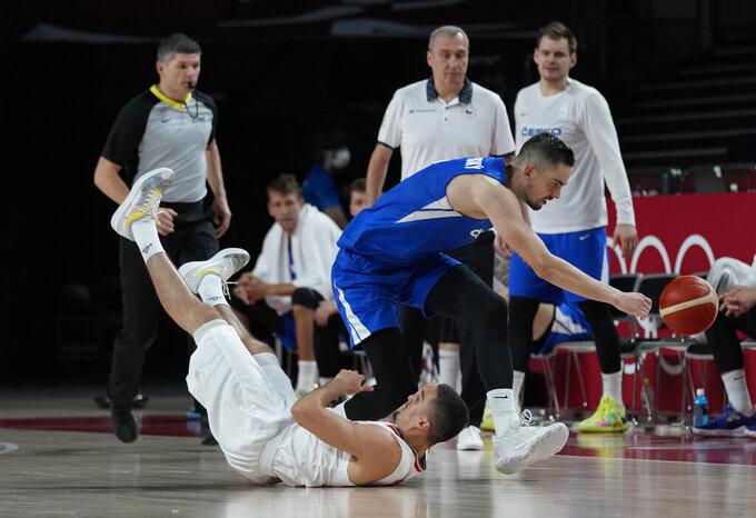 Iran's Pujan Jalalpoor (5) falls as Czech Republic's Tomas Satoransky reaches towards the ball during men's basketball game at the 2020 Summer Olympics, Sunday, July 25, 2021, in Saitama, Japan. (AP Photo/Eric Gay)