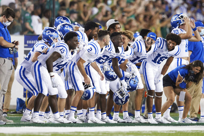 The Duke bench tries to fire up their kickoff team during an NCAA college football game against Charlotte, Friday, Sept. 3, 2021, in Charlotte, N.C. (AP Photo/Brian Westerholt)