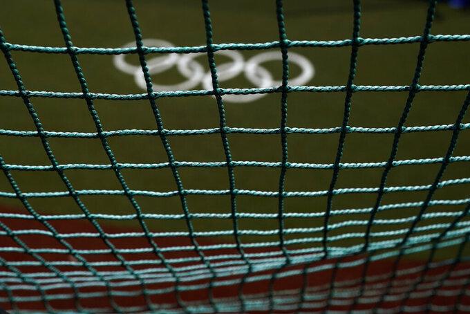 The Olympic rings painted on the field are seen through a net as U.S. softball players take batting practice at the Fukushima Azuma Baseball Stadium ahead of the 2020 Summer Olympics, Tuesday, July 20, 2021, in Fukushima, Japan. (AP Photo/Jae C. Hong)