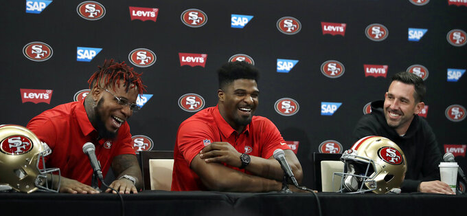 San Francisco 49ers' Kwon Alexander, left, laughs with Dee Ford, center, and coach Kyle Shanahan, right, during an NFL football news conference Thursday, March 14, 2019, in Santa Clara, Calif. (AP Photo/Ben Margot)