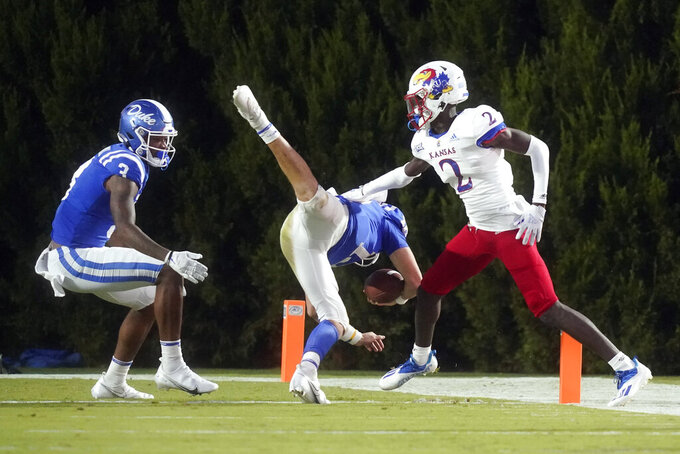 Duke quarterback Gunnar Holmberg (12) scores a touchdown as Kansas cornerback Jacobee Bryant (2) defends with Duke wide receiver Darrell Harding Jr. (3) looking on during the second half of an NCAA college football game in Durham, N.C., Saturday, Sept. 25, 2021. (AP Photo/Gerry Broome)