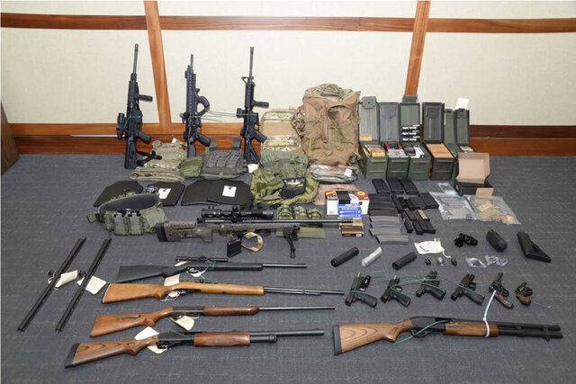 FILE - This file image provided by the Maryland U.S. District Attorney's Office shows a photo of firearms and ammunition that belonged to Christopher Paul Hasson, a Coast Guard lieutenant. Federal prosecutors recommend a 25-year prison sentence for Hasson, accused of stockpiling weapons and targeting Supreme Court justices, prominent Democrats and TV journalists. But defense attorneys dispute the government's claim that he is a domestic terrorist. (Maryland U.S. District Attorney's Office via AP, File)