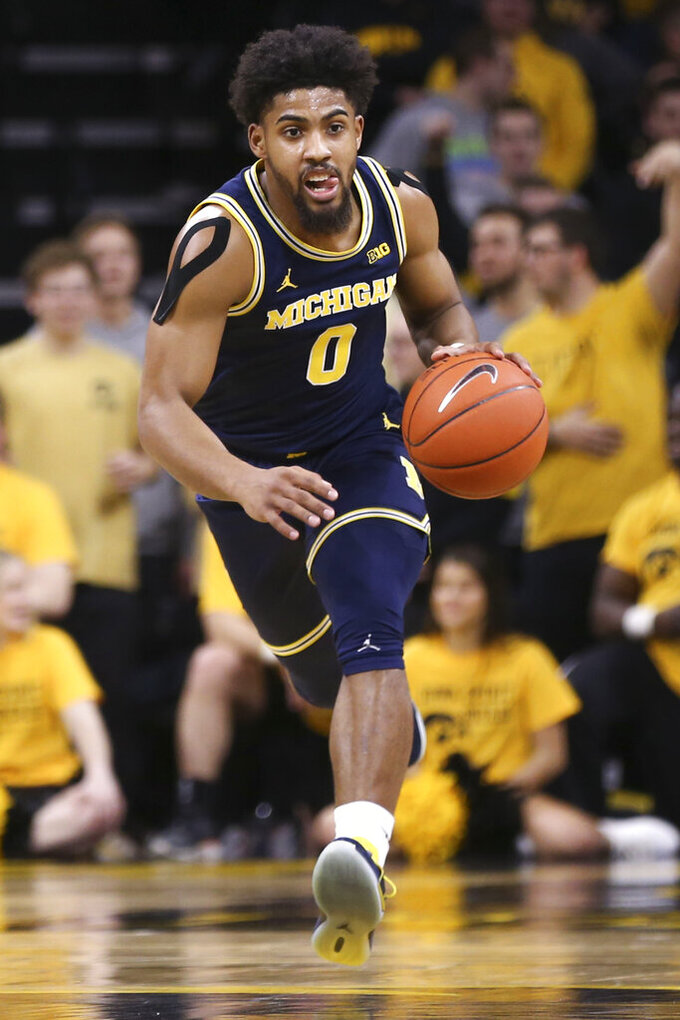 Michigan guard David DeJulius brings the ball up during the first half of an NCAA college basketball game against Iowa on Friday, Jan. 17, 2020, in Iowa City, Iowa. (Rebecca F. Miller/The Gazette via AP)