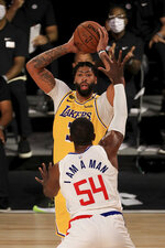 Los Angeles Lakers' Anthony Davis, top, looks to pass against Los Angeles Clippers' Patrick Patterson (54) during the third quarter oof an NBA basketball game Thursday, July 30, 2020, in Lake Buena Vista, Fla. (Mike Ehrmann/Pool Photo via AP)