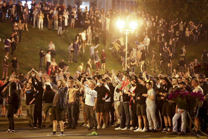 """Protesters shout """"Go away!"""" as they gather after the Belarusian presidential election in Minsk, Belarus, Sunday, Aug. 9, 2020. Belarus police and protesters clashed in the capital and the city of Brest Sunday night after a presidential election in which the country's longtime leader sought a sixth term despite rising discontent with his authoritarian rule and his cavalier dismissal of the coronavirus pandemic. (AP Photo/Sergei Grits)"""