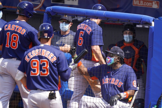 Houston Astros manager Dusty Baker Jr., right, greets Jason Castro (18) and Chas McCormick (6) after they scored on an RBI double hit by Taylor Jones during the sixth inning of a spring training baseball game against the New York Mets, Tuesday, March 16, 2021, in Port St. Lucie, Fla. (AP Photo/Lynne Sladky)