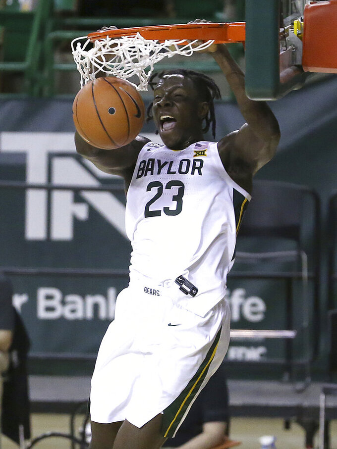 FILE - In this file photo dated Tuesday, Dec. 29, 2020, Baylor forward Jonathan Tchamwa Tchatchoua (23) dunks the ball against Central Arkansas in the first half of an NCAA college basketball game, in Waco, Texas, USA. The NBA's global academy system is beginning to produce high-level collegiate players, as the upcoming NCAA Tournament will include eight NBA Academy alumni. (AP Photo/ Jerry Larson, FILE)