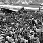 FILE - In this Jan. 23, 1959 file photo, a crowd estimated at more than 20,000 greet Cuban leader Fidel Castro as he waves from a plane upon arrival to Caracas, Venezuela. A little more than two weeks after Castro rode into Havana triumphantly in 1959, he flew to Caracas, where massive crowds lined highways to get a glimpse of the bearded revolutionary whose defeat of the U.S.-backed dictator Fulgencio Batista would inspire a new generation of Latin American leftists. (AP Photo, File)