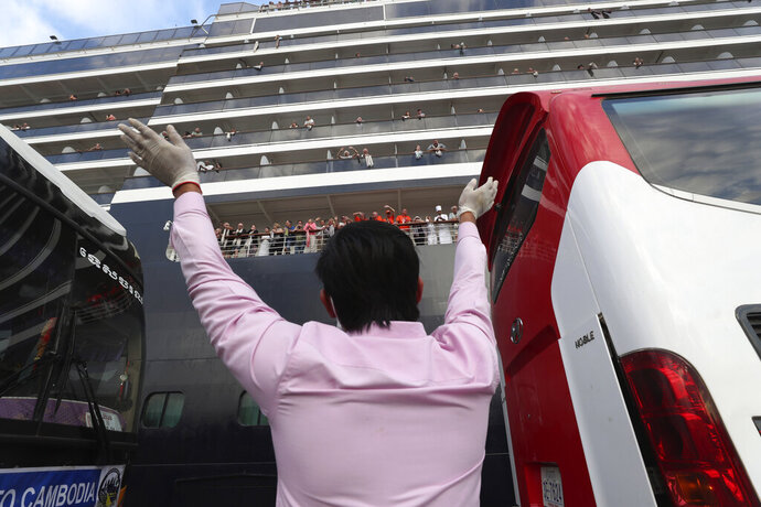 A man waves to passengers of the MS Westerdam, owned by Holland America Line, docked at the port of Sihanoukville, Cambodia, Friday, Feb. 14, 2020. Hundreds of cruise ship passengers long stranded at sea by virus fears cheered as they finally disembarked Friday and were welcomed to Cambodia. (AP Photo/Heng Sinith)