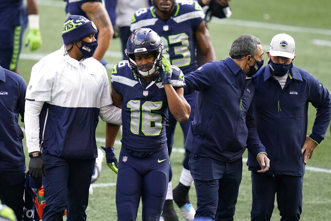 Seattle Seahawks wide receiver Tyler Lockett (16) leaves the field with an injury during the first half of an NFL football game against the New York Giants, Sunday, Dec. 6, 2020, in Seattle. (AP Photo/Elaine Thompson)