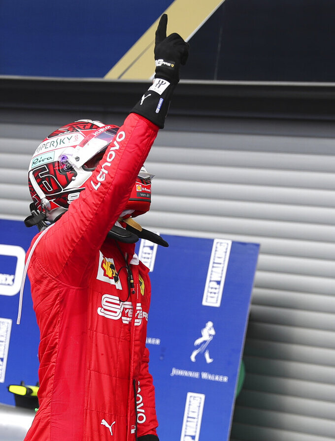 Ferrari driver Charles Leclerc of Monaco jubilates after finishing first in the Belgian Formula One Grand Prix in Spa-Francorchamps, Belgium, Sunday, Sept. 1, 2019. Mercedes driver Lewis Hamilton of Britain placed second and Mercedes driver Valtteri Bottas of Finland placed third. (AP Photo/Francisco Seco)