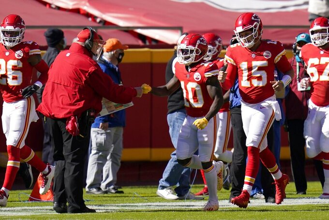 Kansas City Chiefs head coach Andy Reid, left, celebrates with wide receiver Tyreek Hill (10) and quarterback Patrick Mahomes (15) after Hill caught a pass for a touchdown in the first half of an NFL football game against the New York Jets on Sunday, Nov. 1, 2020, in Kansas City, Mo. (AP Photo/Jeff Roberson)
