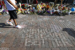 A pedestrian passes a makeshift memorial for the slain and injured victims of a mass shooting that occurred in the Oregon District early Sunday morning, Wednesday, Aug. 7, 2019, in Dayton, Ohio.  Twenty-four-year-old Connor Betts opened fire in Dayton early Sunday, killing several people including his sister, before officers fatally shot him. (AP Photo/John Minchillo)