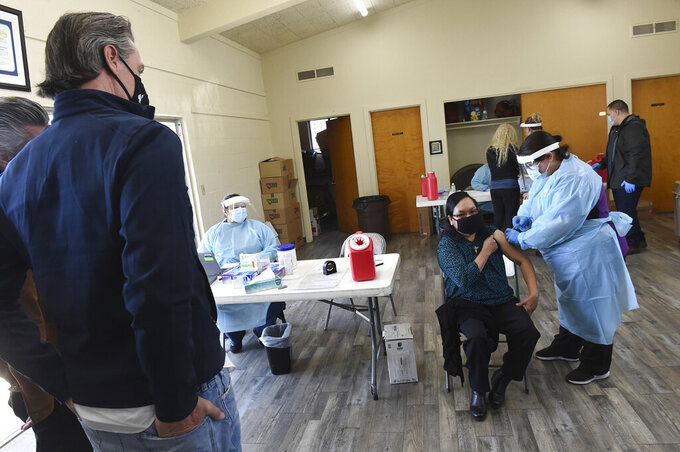 FILE - In this Friday, Feb. 26, 2021, file photo, California Gov. Gavin Newsom watches as a farmworker receive the Pfizer COVID-19 vaccine at a vaccination clinic for farmworkers at the Dr. Sharon Stanley-Rea Community Center in Fresno, Calif. California Gov. Gavin Newsom's administration says the massive new federal coronavirus relief bill will pump more than $150 billion into the state's economy. Nearly half of that money will go to Californians directly in the form of $1,400 stimulus checks and expanded unemployment benefits. Another $26 billion will go to the state government. (John Walker/The Fresno Bee via AP, Pool, File)