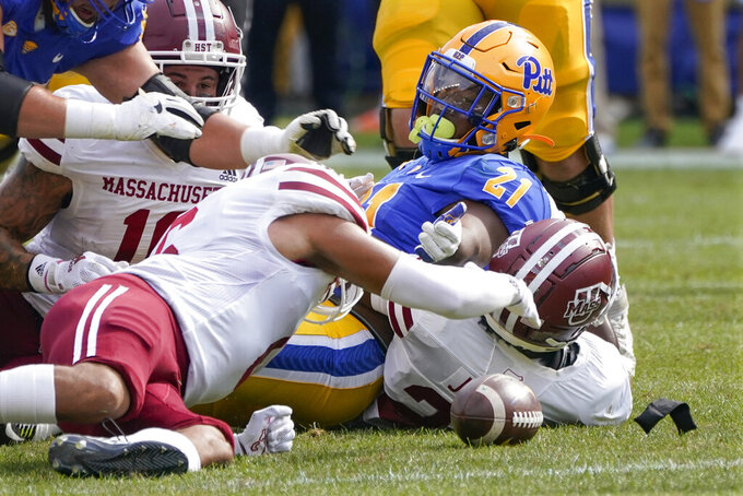 Pittsburgh running back A.J. Davis Jr. (21) reaches for the ball as Massachusetts defensive back Bryson Richardson (6), left, recovers the fumble during the first half of an NCAA college football game, Saturday, Sept. 4, 2021, in Pittsburgh. (AP Photo/Keith Srakocic)