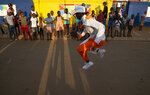 A dancer performs his latest Pantsula dance moves for children in the Orange Farm Township south of Johannesburg, Wednesday, April 14, 2021.  Amid the classes in dancing and marimba music, a leader of the culture group praised Britain's Prince Philip, who died last week and whose Duke of Edinburgh Awards helped to fund the culture group's activities. (AP Photo/Denis Farrell)