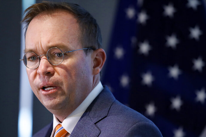 FILE - In this Nov. 27, 2017, file photo, Mick Mulvaney speaks during a news conference after his first day as acting director of the Consumer Financial Protection Bureau in Washington. Tougher rules governing the payday lending industry will remain in place for now after Congress allowed a deadline to overrule them pass without action. It's a rare victory for consumer groups in the era of President Donald Trump. The bureau now under the control of Trump appointee Mulvaney, has already announced plans to revisit the regulations. (AP Photo/Jacquelyn Martin, File)
