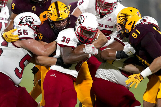 Southern Utah running back David Moore III (30) is stopped by Arizona State defensive lineman D.J. Davidson (98) and defensive end Michael Matus (91) during the first half of an NCAA college football game, Thursday, Sept. 2, 2021, in Tempe, Ariz. (AP Photo/Matt York)