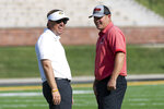 Missouri head coach Eliah Drinkwitz, left, laughs with Southeast Missouri head coach Tom Matukewicz, right, as they watch teams warmup before the start of an NCAA college football game Saturday, Sept. 18, 2021, in Columbia, Mo. (AP Photo/L.G. Patterson)