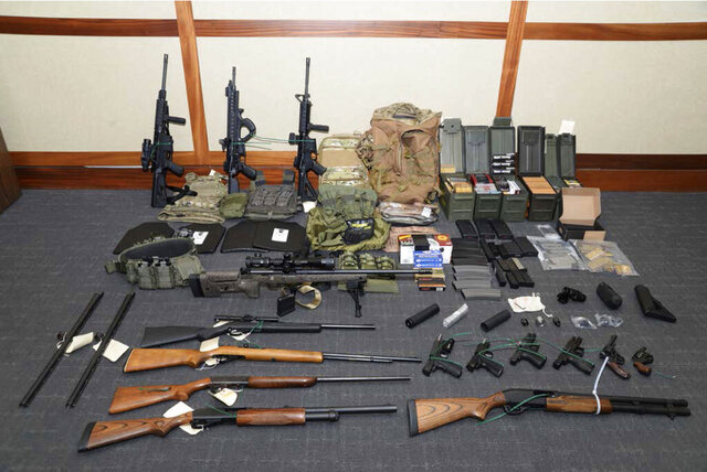 FILE - This undated file image provided by the Maryland U.S. District Attorney's Office shows a photo of firearms and ammunition that was in the motion for detention pending trial in the case against Christopher Hasson.  The Coast Guard lieutenant accused of stockpiling guns and drawing up a hist list of prominent Democrats and TV journalists is scheduled to be sentenced on Friday, Jan. 31, 2020 for his guilty plea to firearms and drug offenses. (Maryland U.S. District Attorney's Office via AP, File)