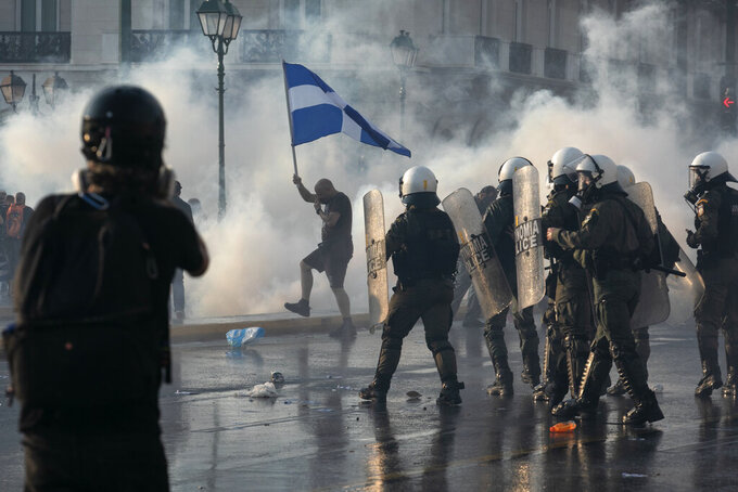 Greek police use tear gas to disperse anti-vaccine protesters during a rally at Syntagma square, central Athens, on Wednesday, July 21, 2021. Thousands of people protested against Greek government's measures to curb rising COVID-19 infections and drive up vaccinations in the country where almost 50% of Greeks and country residents have received at least one dose of the vaccine. (AP Photo/Yorgos Karahalis)