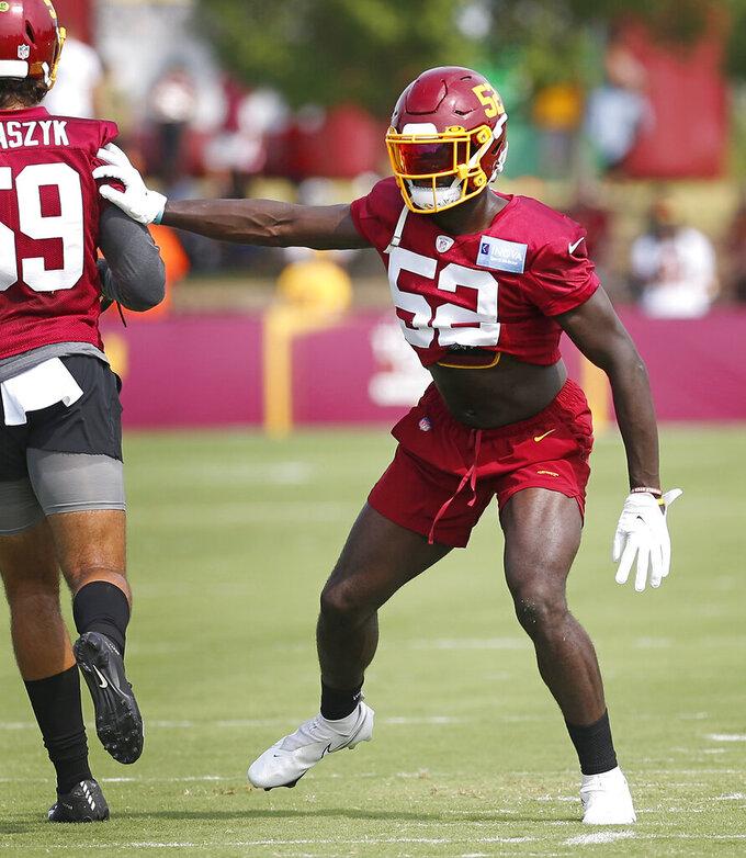 Linebacker Jamin Davis (52) creates space in a drill during the Washington Football Team's NFL training camp Saturday, July 31, 2021, in Richmond, Va. (AP Photo/Dean Hoffmeyer)