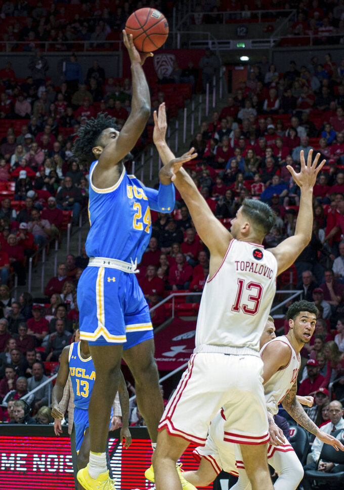 UCLA guard Jalen Hill (24) is fouled while shooting by Utah forward Novak Topalovic (13) in the first half of an NCAA college basketball game Saturday, March 9, 2019, in Salt Lake City. (AP Photo/Tyler Tate)