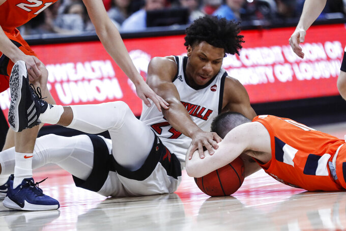 Louisville forward Dwayne Sutton (24) battles for the ball with Syracuse guard Joseph Girard III (11) during the first half of an NCAA college basketball game Wednesday, Feb. 19, 2020, in Louisville, Ky. (AP Photo/Wade Payne)