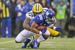 Green Bay Packers' Kenny Clark, top, tackles New York Giants' Saquon Barkley during the first half of an NFL football game, Sunday, Dec. 1, 2019, in East Rutherford, N.J. (AP Photo/Adam Hunger)