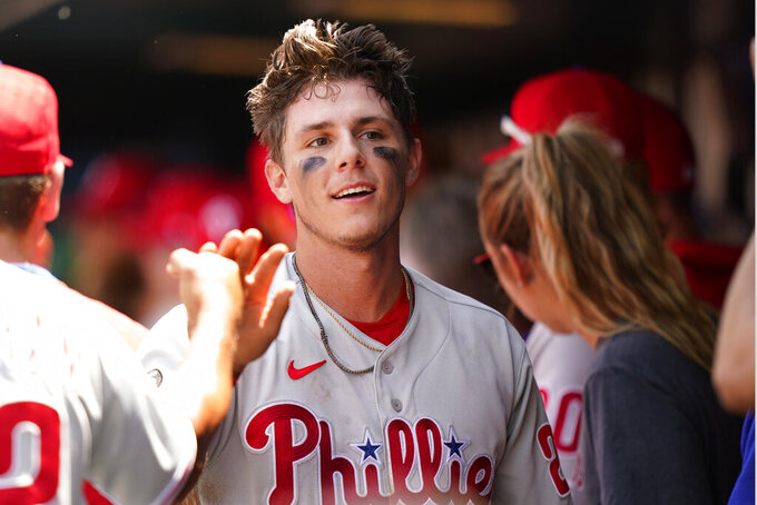 Philadelphia Phillies players and coaches greet Philadelphia Phillies' Nick Maton, center, in the dugout after Maton scored on Odubel Herrera's second-inning sacrifice fly during a baseball game, Sunday, June 27, 2021, in New York. (AP Photo/Kathy Willens)