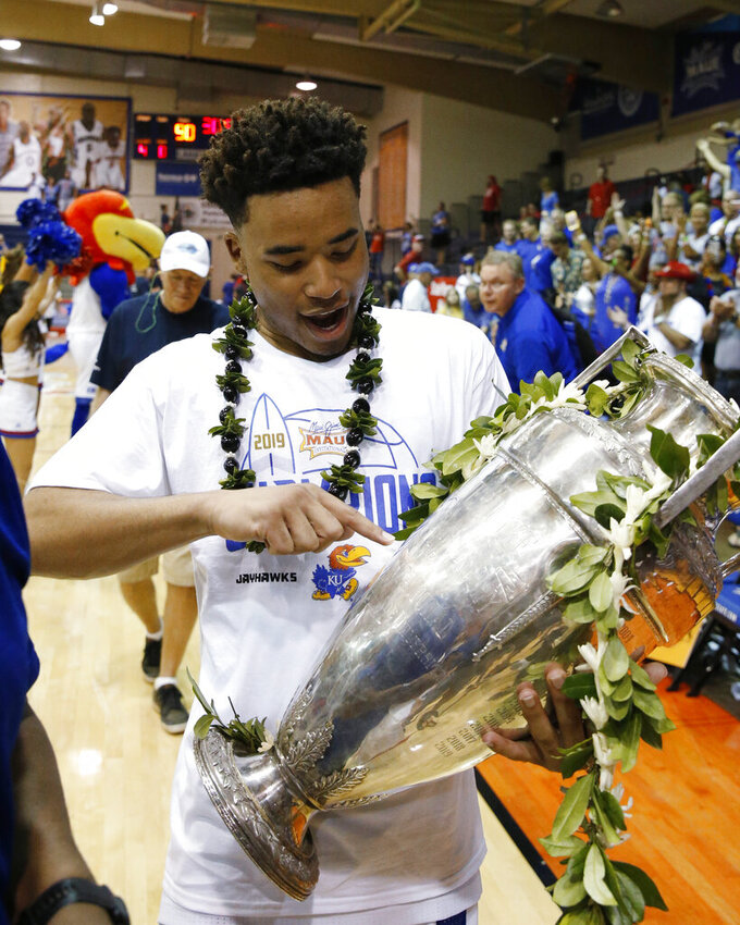 Kansas guard Devon Dotson holds the Maui Invitational trophy Wednesday, Nov. 27, 2019, in Lahaina, Hawaii. Kansas defeated Dayton in 90-84 in overtime in an NCAA college basketball game for the title. (AP Photo/Marco Garcia)