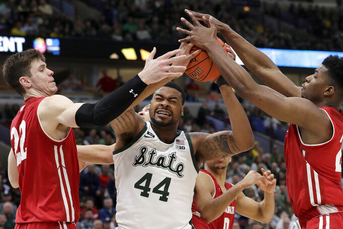 Michigan State's Nick Ward (44) battles for a rebound against Wisconsin's Ethan Happ (22) and Aleem Ford (2) during the second half of an NCAA college basketball game in the semifinals of the Big Ten Conference tournament, Saturday, March 16, 2019, in Chicago. Michigan State won 67-55. (AP Photo/Nam Y. Huh)