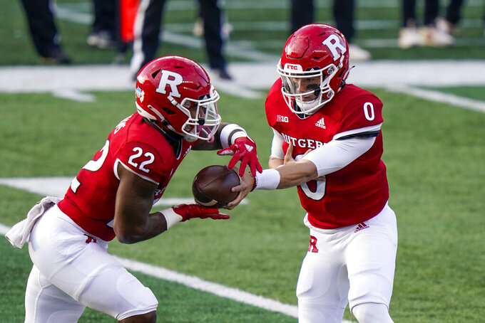 Rutgers quarterback Noah Vedral (0) hands to running back Kay'Ron Adams (22) during the second quarter of the team's NCAA college football game against Indiana, Saturday, Oct. 31, 2020, in Piscataway, N.J. (AP Photo/Corey Sipkin)
