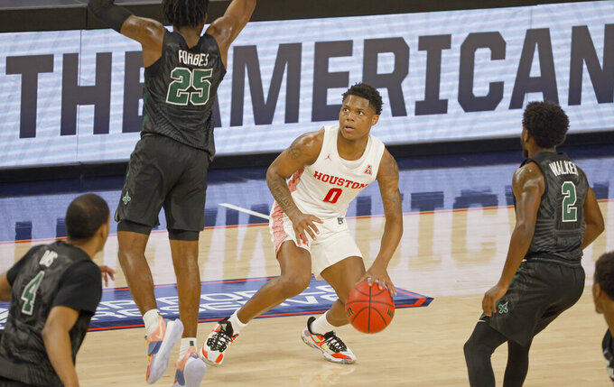 Houston guard Marcus Sasser (0) tries to line up a last-second shot as Tulane guard Jaylen Forbes (25), forward Nobal Days (4) and guard Jordan Walker (2) defend during the first half of an NCAA college basketball game in the quarterfinal round of the American Athletic Conference men's tournament Friday, March 12, 2021, in Fort Worth, Texas. (AP Photo/Ron Jenkins)