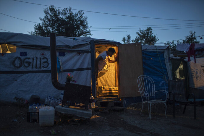 In this Thursday Oct. 3, 2019 photo, an Afghan man looks out of his tent in a makeshift refugee and migrant camp on the fringes of the overcrowded Moria camp on the Greek island of Lesbos. Greece's conservative government announced Wednesday Nov. 20, 2019, plans to overhaul the country's migration management system, and replacing existing camps on the islands with detention facilities and moving and 20,000 asylum seekers to the mainland over the next few weeks. (AP Photo/Petros Giannakouris)