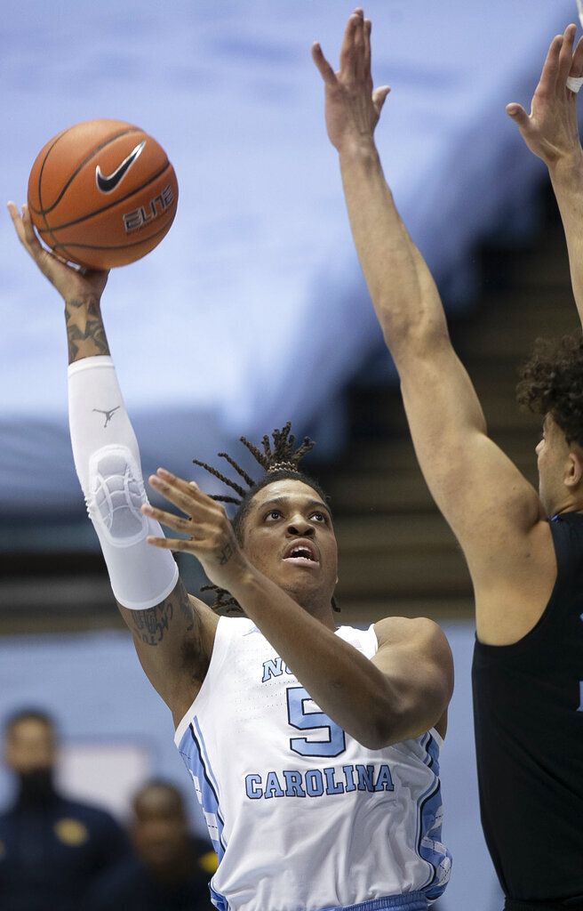 North Carolina's Armando Bacot (5) shoots against Marquette's Dawson Garcia (33) during the first half of an NCAA college basketball game Wednesday, Feb. 24, 2021, in Chapel Hill, N.C. (Robert Willett/The News & Observer via AP)