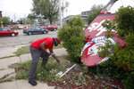 Forrest Marshall, the breakfast crew chief at a Wendy's, picks up letters from a sign that was toppled in Cedar Rapids, Iowa, after a powerful storm moved through the state Monday, Aug. 10, 2020. Marshall said he had just finished putting up new lettering on the sign when the storm moved in.