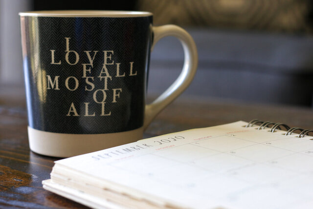 Associated Press journalist Cheyanne Mumphrey opens her planner to the month of September with a cup of hot chocolate in her studio in downtown Phoenix on Sept. 1, 2020. (AP Photo/Cheyanne Mumphrey)